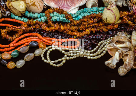 Bright old beads of turquoise, red coral, amber, pomegranate, colorful agate, pearls among dry buds and seashells on a black background - Stock Photo