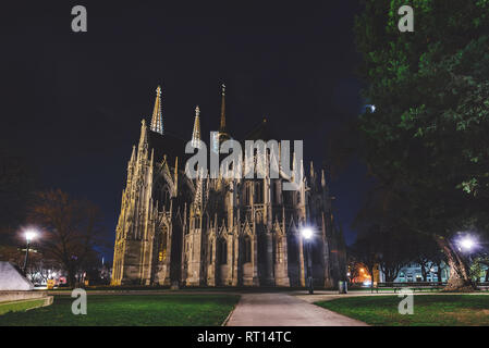 Vienna, Austria - December 25, 2017. Neo - gothic twin tower Votivkirche Illuminated at Night with no people. Facade of gothic Votive church, trees an - Stock Photo