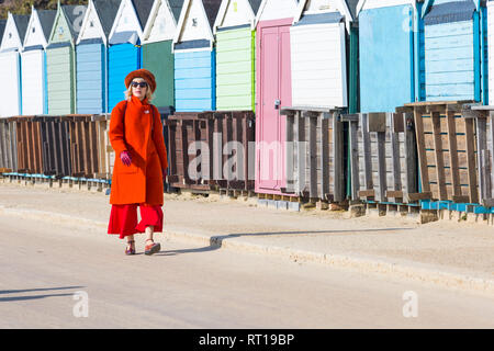 Bournemouth, Dorset, UK. 27th Feb, 2019. UK weather: warm weather continues with another lovely warm sunny day at Bournemouth as visitors enjoy the sunshine at the seaside. Bournemouth beach is voted the best beach in the UK. Lady in red enjoys a walk along the promenade. Credit: Carolyn Jenkins/Alamy Live News - Stock Photo
