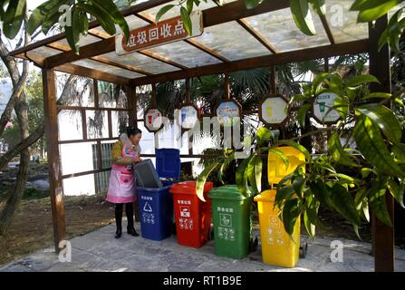 (190227) -- BEIJING, Feb. 27, 2019 (Xinhua) -- A woman puts trash into a classified garbage bin at Gunan Village of Gaohu Township in Jing'an County, east China's Jiangxi Province, Jan. 23, 2019. The 19th National Congress of the Communist Party of China (CPC), which was convened in October 2017, for the first time proposed pursuing a rural vitalization strategy and made it clear that the development of agriculture and rural areas must be prioritized. Revitalized rural areas spring up as the implementation of rural vitalization strategy is being accelerated across the country following the pri - Stock Photo