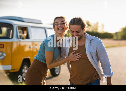 Happy couple doing a road trip with a camper, embracing on the road - Stock Photo