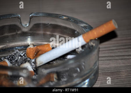 Burning cigarette in glass ashtray with butts - Stock Photo
