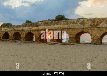 Sunset view of the beach and the Roman Aqueduct in Caesarea, Northern Israel. Its and ancient water supply system - Stock Photo
