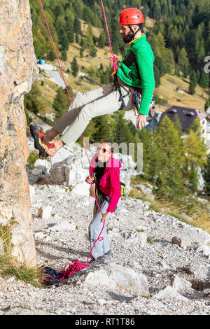 Italy, Cortina d'Ampezzo, man abseiling in the Dolomites mountains with the assistance of a woman - Stock Photo