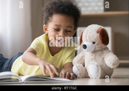 Happy african little boy playing alone reading book to toy - Stock Photo