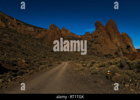 Volcanic landscape and track lit by the full moon in the middle of the night at the Las Canadas del Teide national park, Tenerife, Canary Islands, Spa - Stock Photo