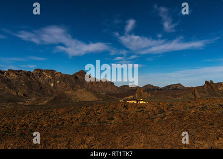 The Parador hotel in the volcanic landscape lit by the full moon in the middle of the night at the Las Canadas del Teide national park, Tenerife, Cana - Stock Photo
