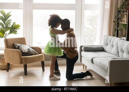 Affectionate loving black dad embracing kid girl standing on knee