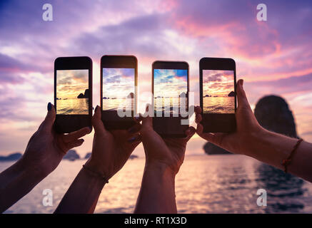 Closeup photo of four hands with mobile phones taking photo of beautiful sunset over sea bay - Stock Photo