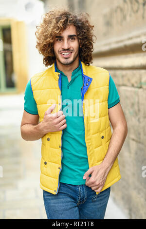 Portrait of smiling young man with curly hair wearing yellow waistcoat outdoors - Stock Photo