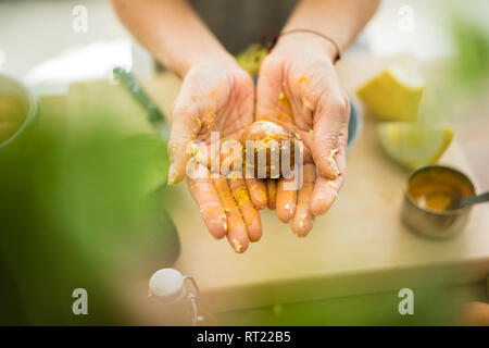 Messy hands holding avocado pit - Stock Photo