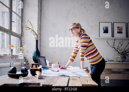 Portrait of smiling woman standing at desk in a loft looking through window - Stock Photo