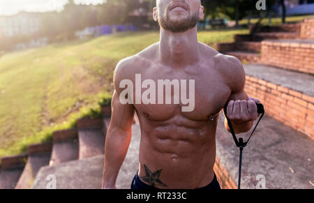 Mid-section of barechested muscular man exercising with expander outdoors - Stock Photo