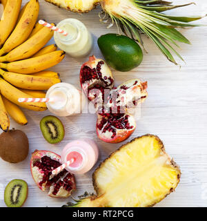 Fruit smoothies of different tastes in glass bottles with ingredients on white wooden surface. Flat lay. From above. Close-up. - Stock Photo