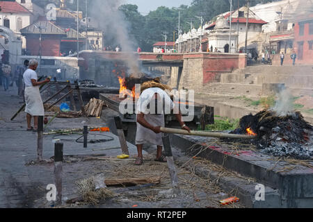 Men from the (Hindu) Dom caste stoking funeral pyres by the Bagmati River on the grounds of Pashupatinath Temple, Kathmandu, Nepal - Stock Photo