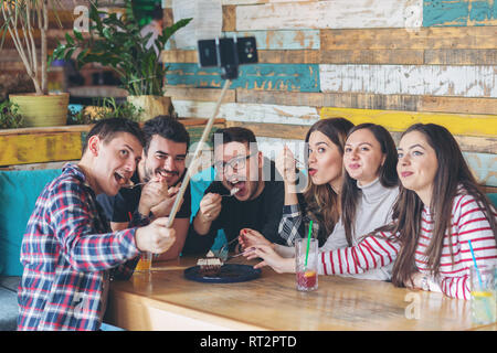 Happy friends having fun together taking selfie while sharing chocolate cake. Young people addicted by sharing stories on social network community - M - Stock Photo