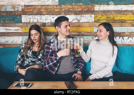 Happy young girl drinking beer with young man and socialise ignoring other jealous sad woman sitting next to them at rustic bar restaurant. Love and j