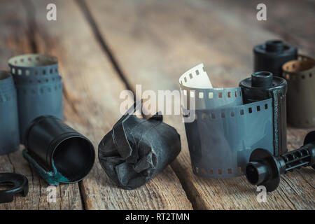 Vintage photo film rolls and cassette on old wooden desk. Retro toned. - Stock Photo