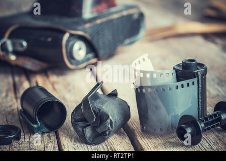 Old photo film rolls and cassette, vintage camera on background. Retro toned. - Stock Photo