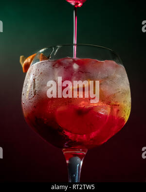 Cocktail with green and red gradient background. - Stock Photo