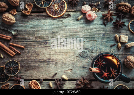 Mulled wine in rustic mug with spices and ingredients on wooden background. Top view, flat lay. Retro styled photo. Copy space for your text. - Stock Photo