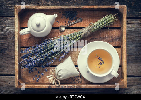 Bunch of lavender flowers, healthy tea in cup, teapot and sachets filled with dried lavender in wooden tray. Retro toned. Top view. Flat lay. - Stock Photo