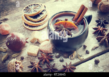 Mulled wine in black mug and ingredients on table. Retro toned. - Stock Photo