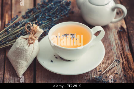 Bunch of lavender flowers, healthy tea in cup, teapot and sachets filled with dried lavender. Retro toned. - Stock Photo