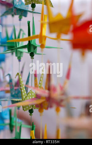 Several swans of decorative colors made in paper. Colorful origami from Japan. Paper folded into animal shapes. Some silhouettes out of focus. Neutral - Stock Photo