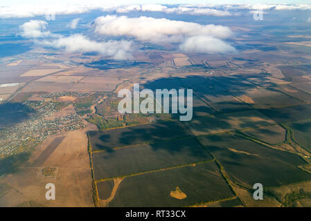 Aerial photography above cloud with big river among square green field of agriculture in countryside.