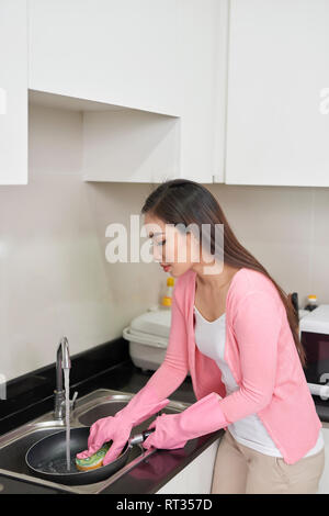 girl housewife washes dirty dishes in the kitchen - Stock Photo