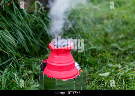 Fodable camping kettle with boiling water standing on burning stove. - Stock Photo