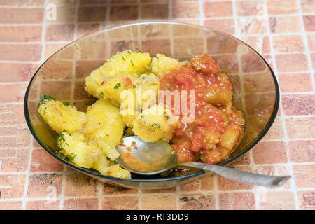 Potatoes with vegetables in a plate with a spoon on table - Stock Photo
