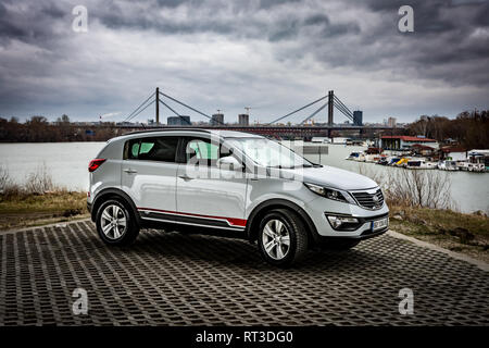 SUV Kia Sportage 2.0 CRDI awd or 4x4, white color, parked on the banks of the river Sava, on the stormy weather with gloomy clouds. - Stock Photo