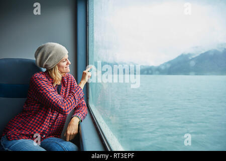 Chile, Hornopiren, woman drawing a heart on the window of a ferry - Stock Photo