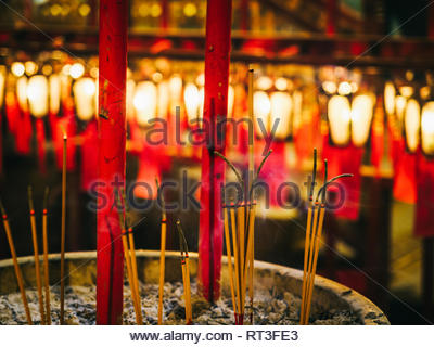 Incense burning inside the Man Mo temple, Hong Kong Island with chinese lanterns in the background - Stock Photo