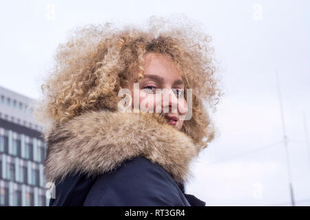 Portrait of smiling blond woman with ringlets wearing fur collar