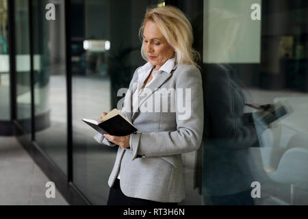 Senior businesswoman leaning against glass front checking diary - Stock Photo