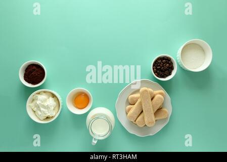 Ingredients for cooking tiramisu: sponge fingers cookies (Savoiardi, Ladyfinger, biscuit), mascarpone, cream, sugar, cocoa, coffee and egg on blue bac - Stock Photo