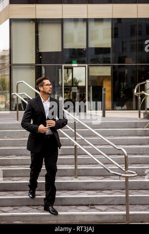 Businessman with earbuds walking on stairs in the city - Stock Photo