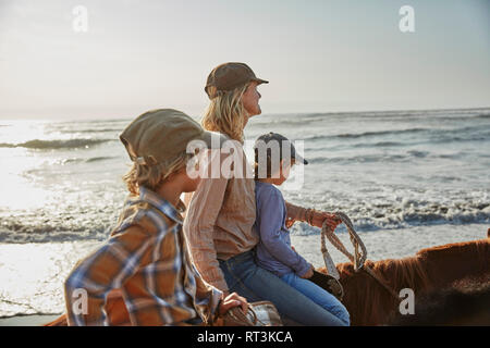 Chile, Vina del Mar, mother with two sons riding horses on the beach - Stock Photo