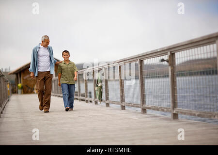 Portrait of a young boy walking along a pier with his mature grandfather. - Stock Photo