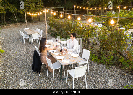 Italy, Tuscany, Siena, young couple having dinner in a vineyard - Stock Photo