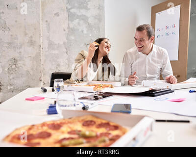 Laughing colleagues having lunch break with pizza in conference room - Stock Photo