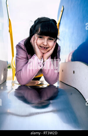 Portrait of girl leaning on slide of a  playground - Stock Photo