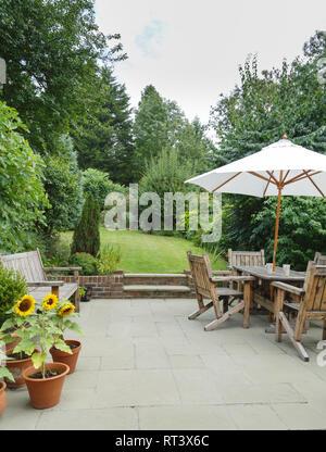 Garden in summer with patio, wooden garden furniture and a parasol or sun umbrella - Stock Photo