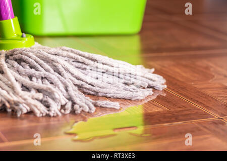 Rope mop on the tile floor and a puddle of water. - Stock Photo