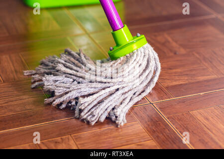 Rope mop wipes the floor of the tile. - Stock Photo