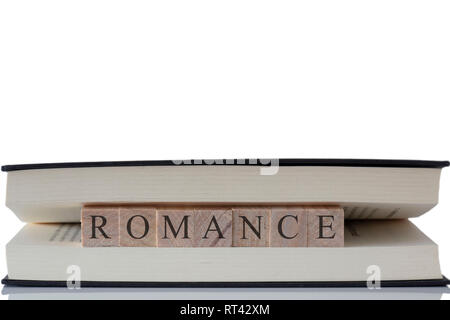 Romance written on wooden blocks inside a book isolated on a white background with reflection - Stock Photo