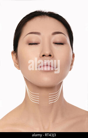asian woman with arrows on her face over white background. neck lifting concept. correction of double chin - Stock Photo